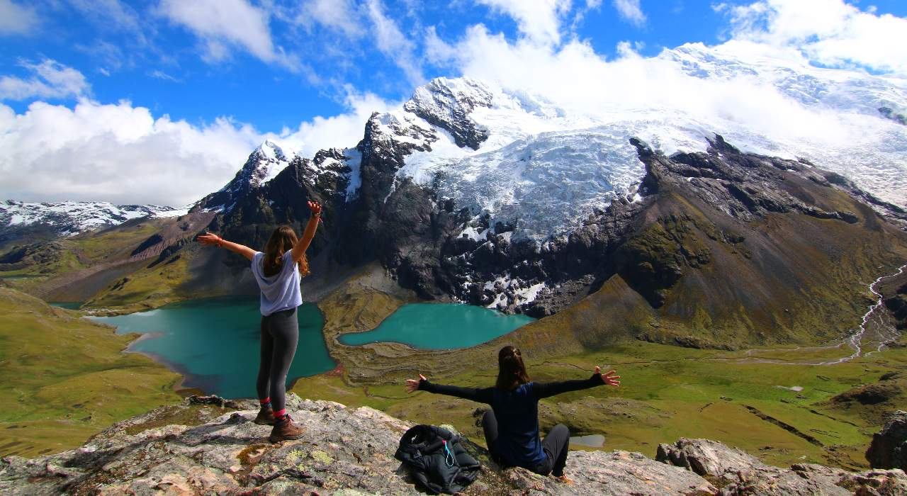 One person jumps and another sits on a rock overlooking to cobalt lakes and the Ausangatecocha mountain behind in Peru
